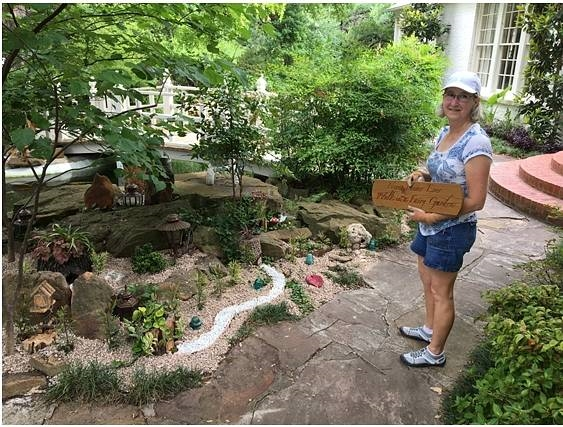 Carol Welch adds the final touches to the new Fairy Garden.